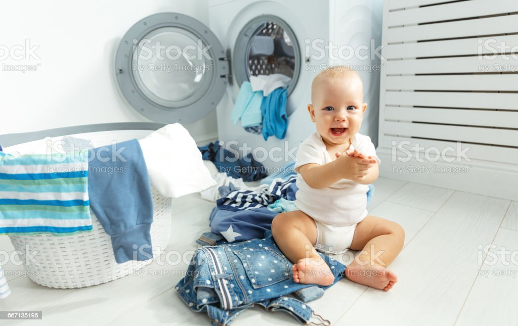 fun happy baby boy to wash clothes and laughs in laundry stock photo