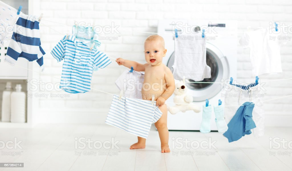 fun happy baby boy to wash clothes and laughs in laundry royalty-free stock photo