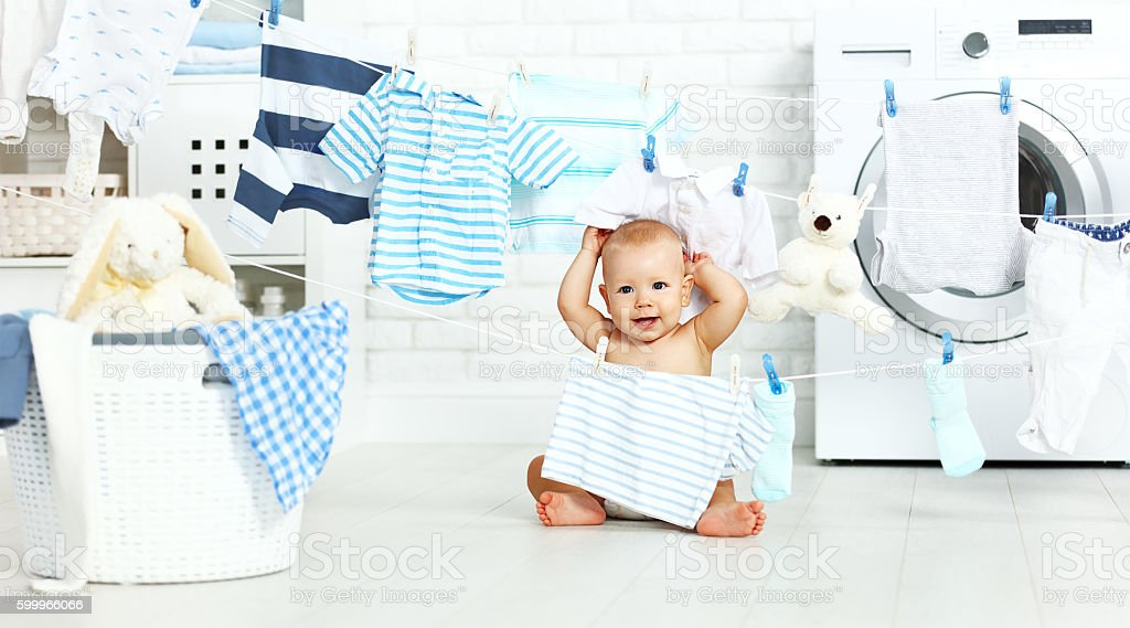 fun happy baby boy  to wash clothes  in laundry stock photo