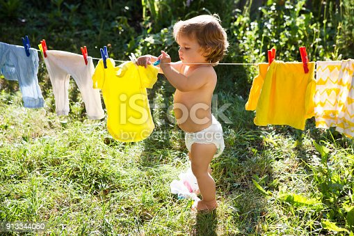 istock fun happy baby girl to wash clothes and laughs  in the meadow on a sunny summer day 913344050