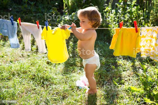 Fun happy baby girl to wash clothes and laughs in the meadow on a picture id913344050?b=1&k=6&m=913344050&s=612x612&h=oayrdr6c snpquzlkwputaum9wh 3xrkkq3znbk41vw=