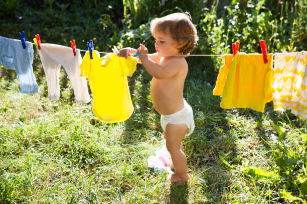Fun happy baby girl to wash clothes and laughs in the meadow on a picture id913344050?b=1&k=6&m=913344050&s=612x612&w=0&h=zdm5dw5idtxbcqxuzykmykcsynqrzs1utdgs2jp t54=