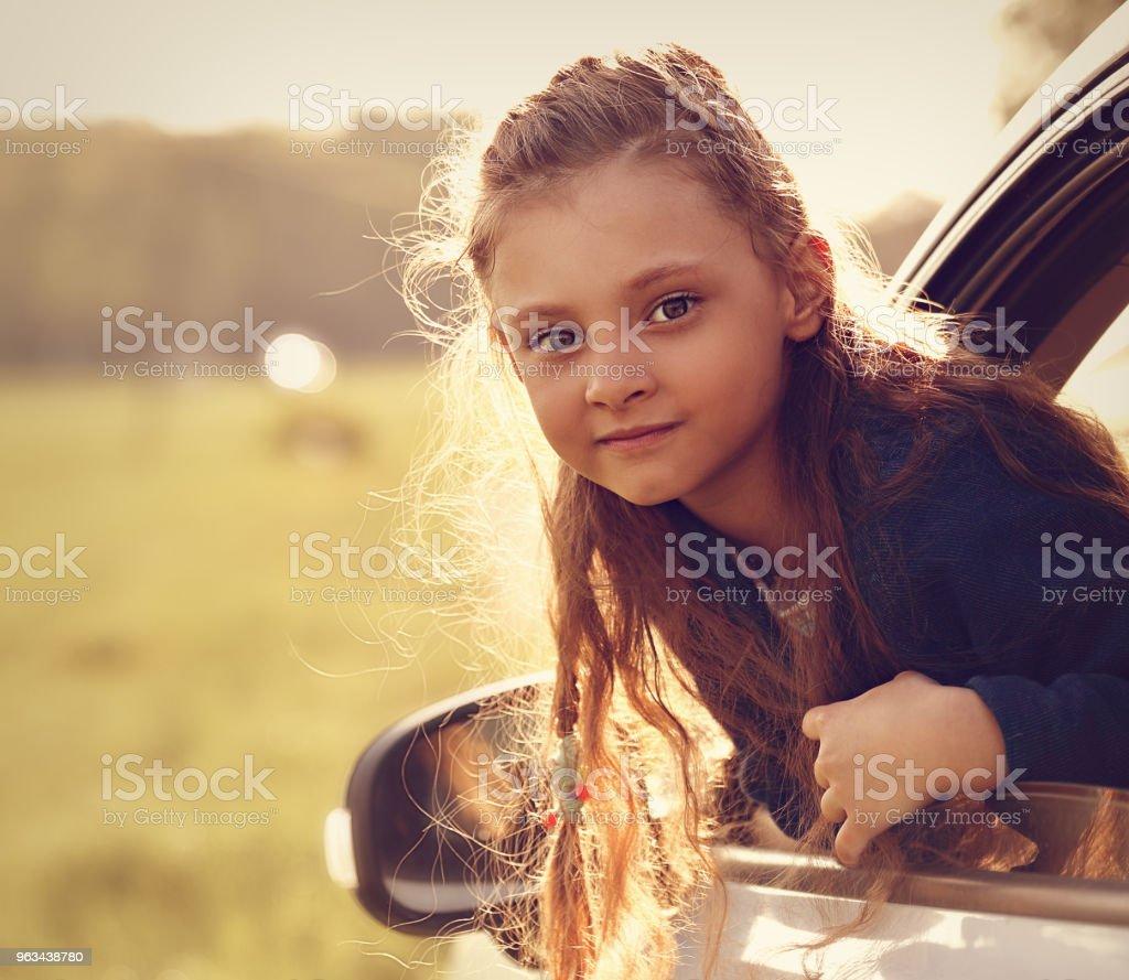 Fun happy traveling kid girl looking from the car window on summer bright green nature background. Toned closeup portrait - Zbiór zdjęć royalty-free (Dziecko)