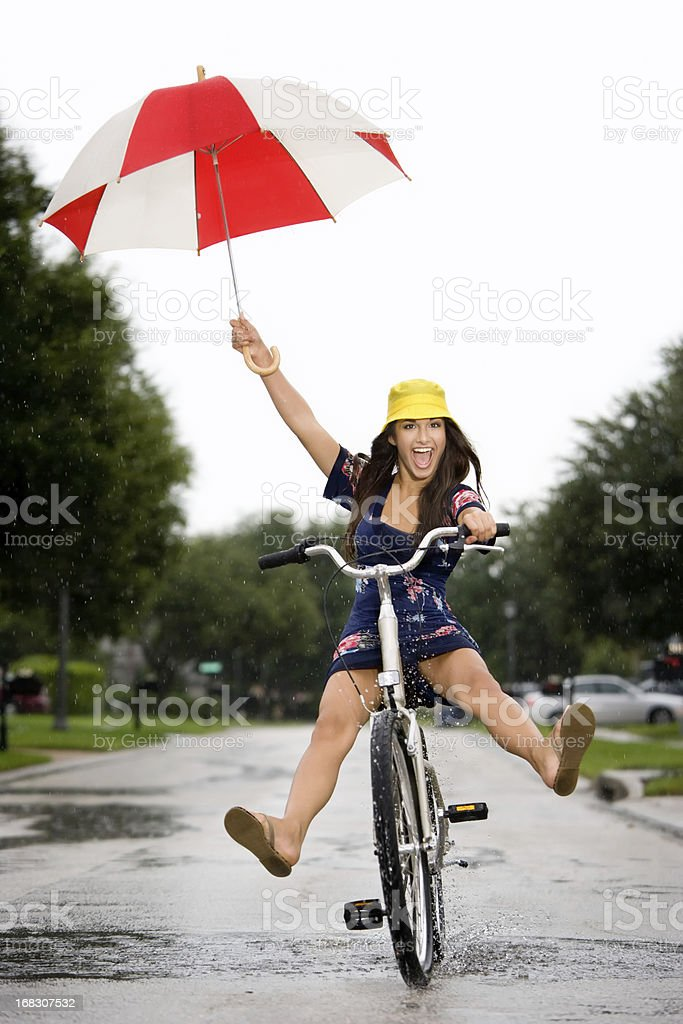 Young attractive girl riding a bicycle in a summer rain shower.