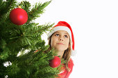 A young girl, with a Santa Claus hat hiding behind the  Christmas tree.