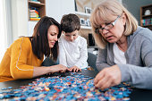 Toddler boy with his mother and grandmother doing a jigsaw puzzle at home in quarantine during coronavirus crisis