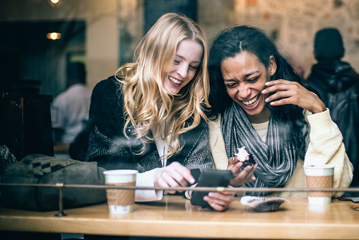 Two multiethnic young female friends having fun, rejoicing memories using a smart phone while enjoying coffee and pastries in the local NYC coffee shop, natural light, taken from the street.