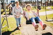 Little girl being pushed on a swing set by her Mother.