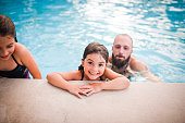 Man in his thirties with two children playing in a pool, they are happy and smiling, cheerful and candid. Togetherness perhaps on a vacation