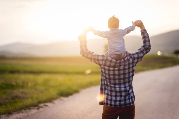 Fun in the spring Father carries his baby boy on his shoulders while they are walking and having fun on the country road piggyback stock pictures, royalty-free photos & images