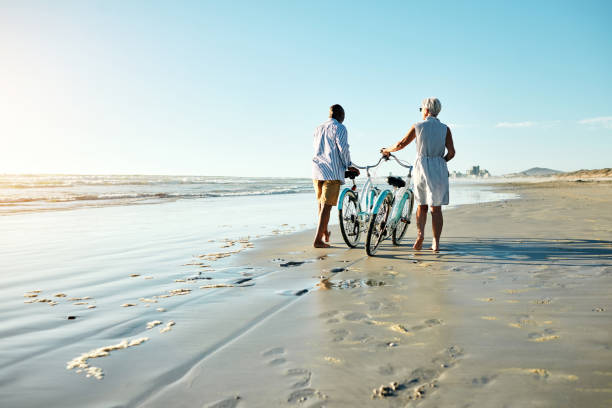 Fun is for everyone Shot of a senior couple riding their bicycles at the beach retirement stock pictures, royalty-free photos & images