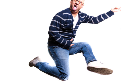 A crazy young man playing air guitar while jumping in mid air. Shot on a white background, and isolated in post processing.