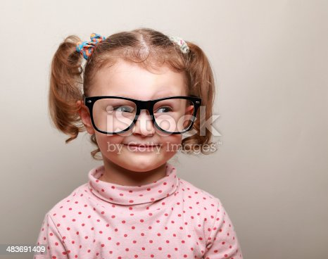 istock Fun kid girl in glasses looking on empty copy space 483691409