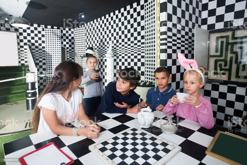 fun kids discuss the game in the chess quest room stock photo
