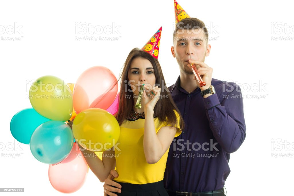 fun loving couple celebrating birthday held in hand balls and blow horns stock photo