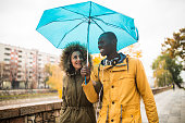 Photography of a multi-ethnic couple walking in rain and sharing an umbrella, laughing and having fun