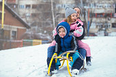 Cheerful young mother have a fun with her kids on snow
