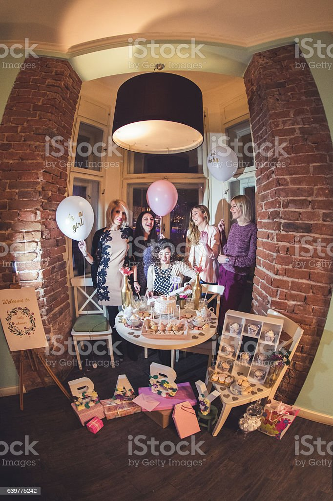 Friends celebrating pregnant woman\'s baby shower and giving her gifts