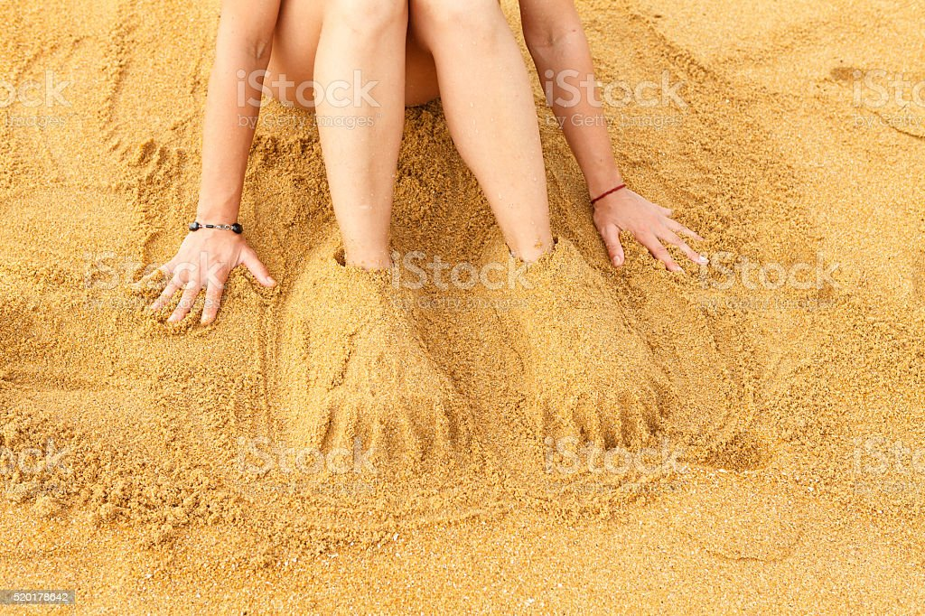 Fun on the beach - human legs covered with sand stock photo