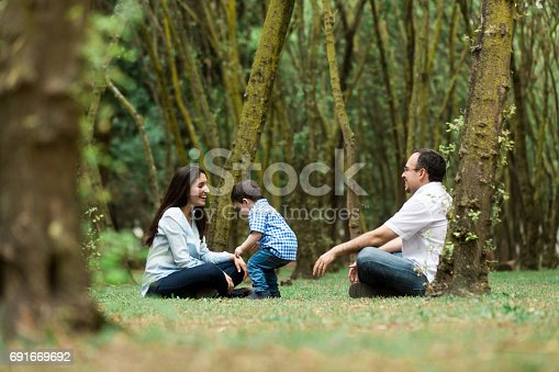 811227514 istock photo Fun parents playing with little boy outdoors 691669692