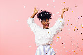 Fun party girl, smiling woman throwing confetti, isolated on pink studio background
