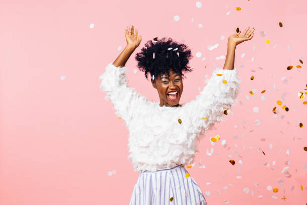 fun party girl, smiling woman throwing confetti - carlos david stock pictures, royalty-free photos & images
