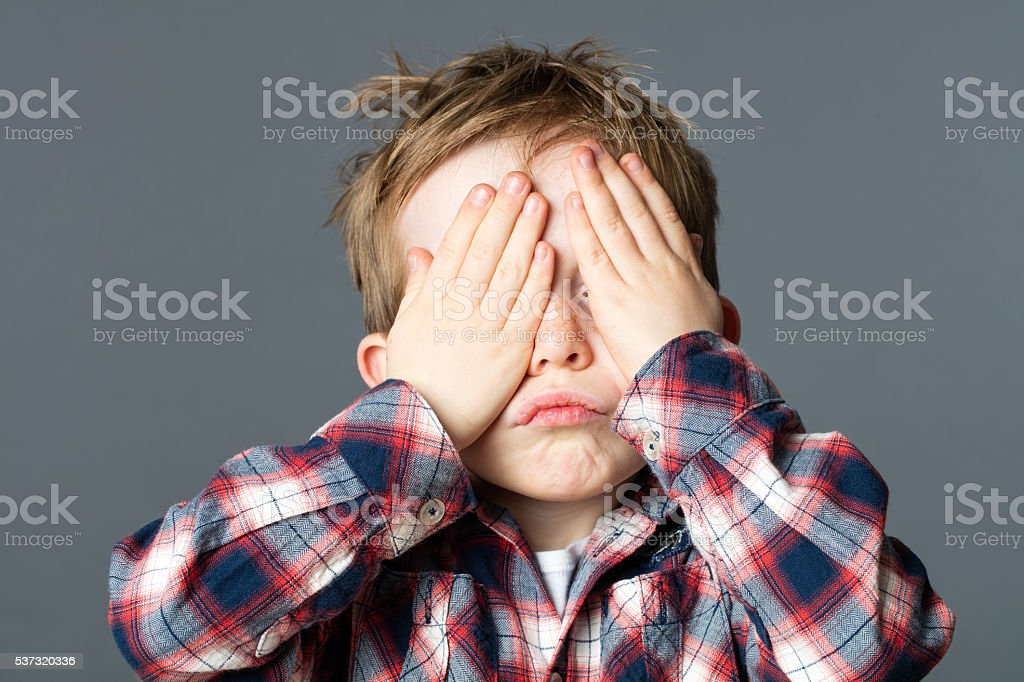 fun peekaboo for kid covering his eyes to be invisible stock photo