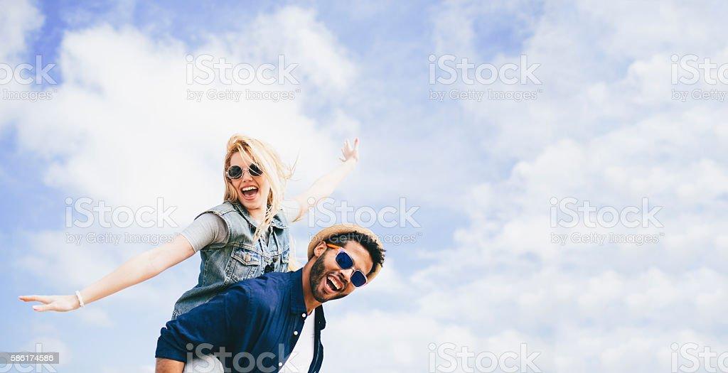 Fun piggyback against a cloudy blue sky – Foto