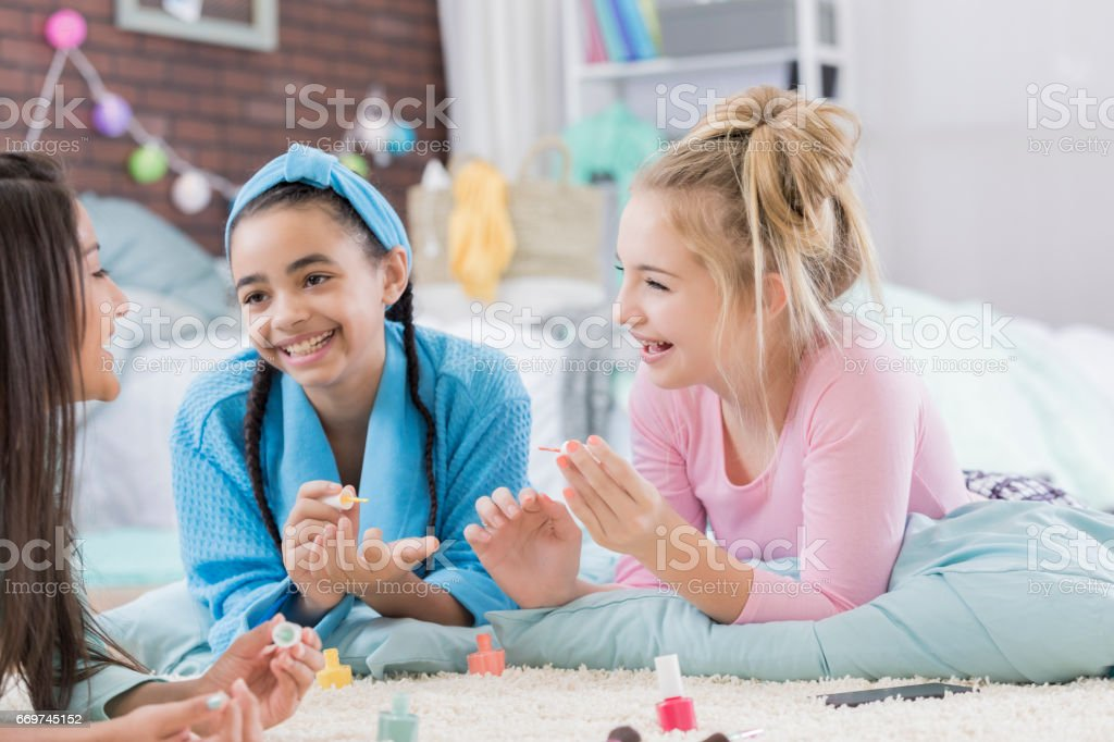 Fun preteen friends paint fingernails during sleepover stock photo
