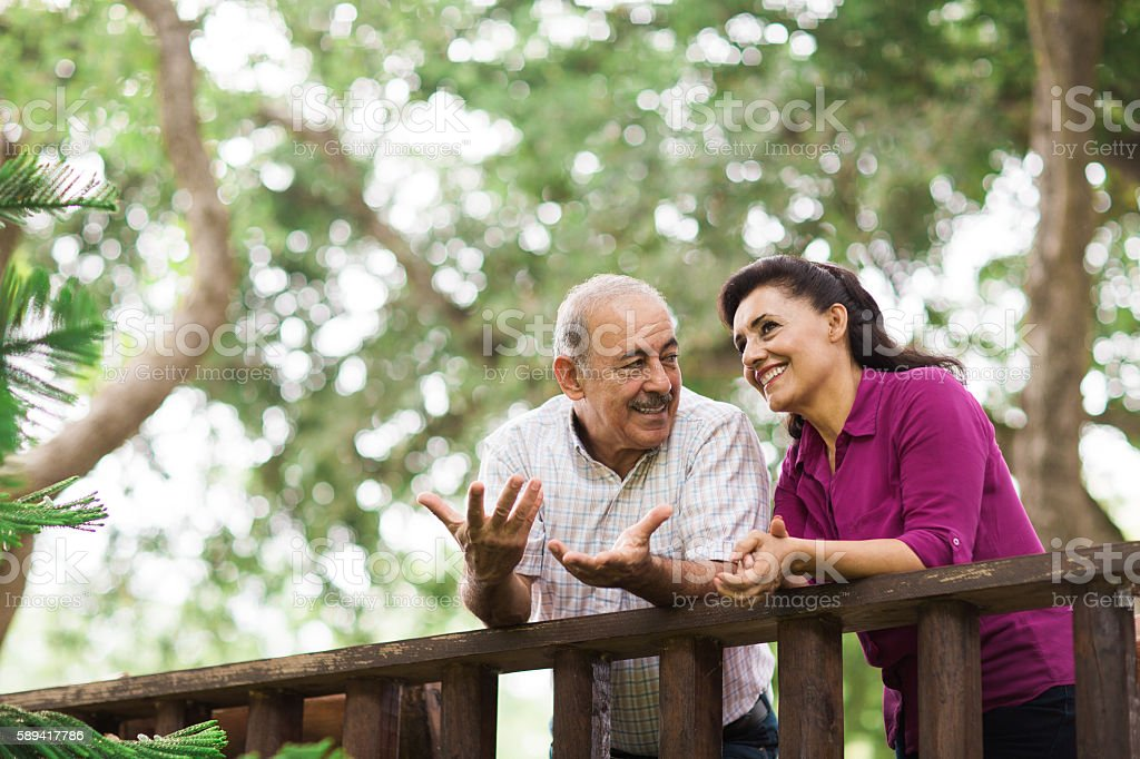 Fun senior latin couple conversing outdoors stock photo