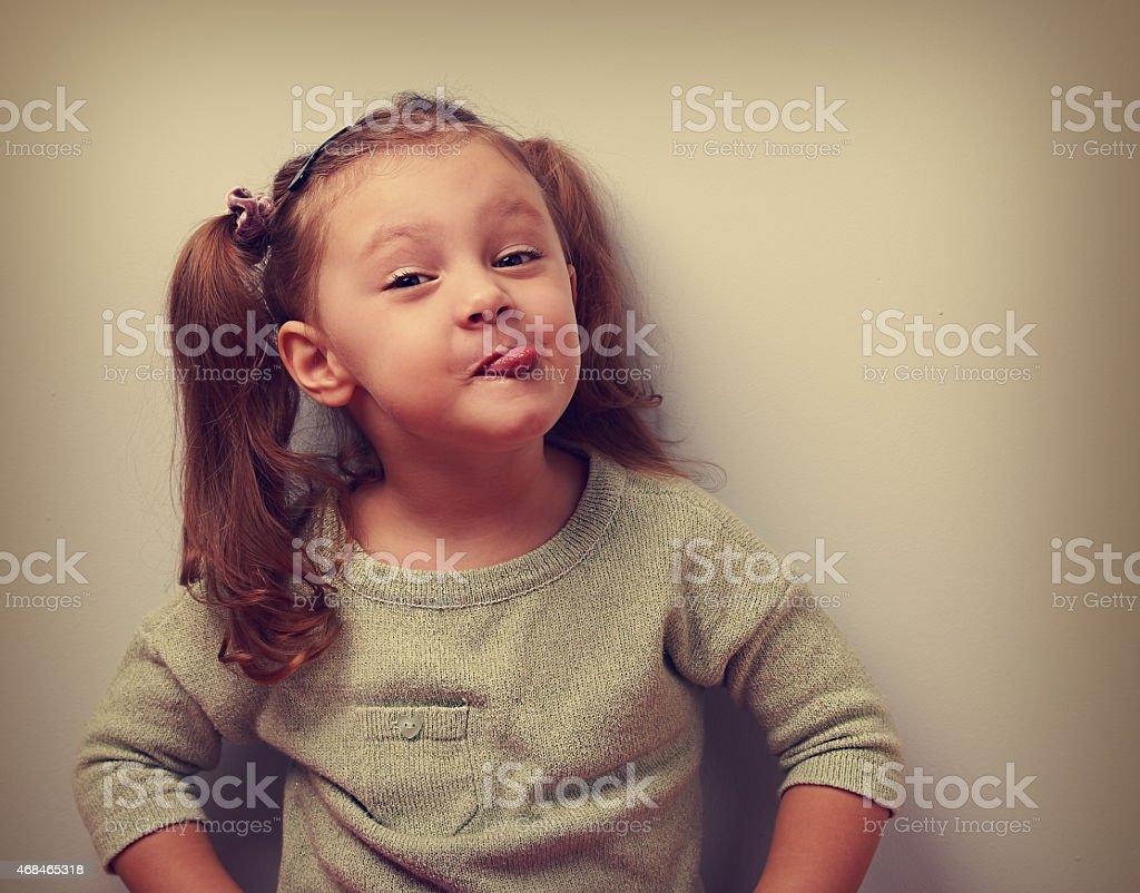 Fun smiling girl grimacing showing the tongue. Closeup vintage stock photo