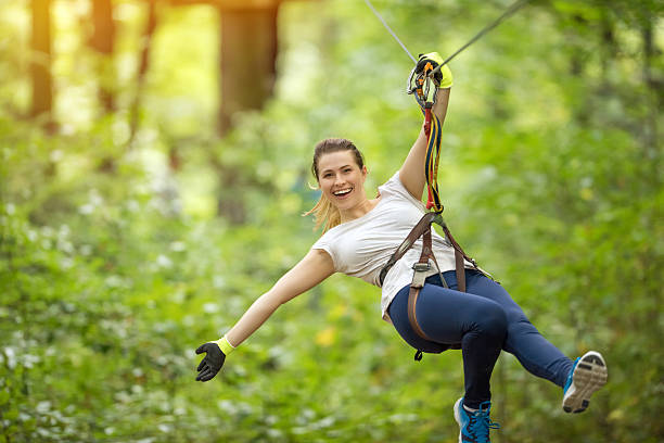 fun time in tyrolean traverse adventure park in the forest, happy woman on tyrolean traverse enjoying her day and laughing. zip line stock pictures, royalty-free photos & images