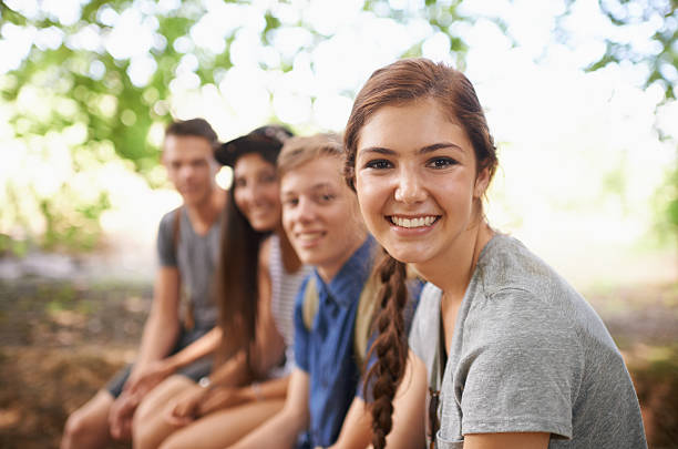 Fun times in the fresh air Portrait of a teenage girl sitting with her friends in the outdoors teenagers only stock pictures, royalty-free photos & images