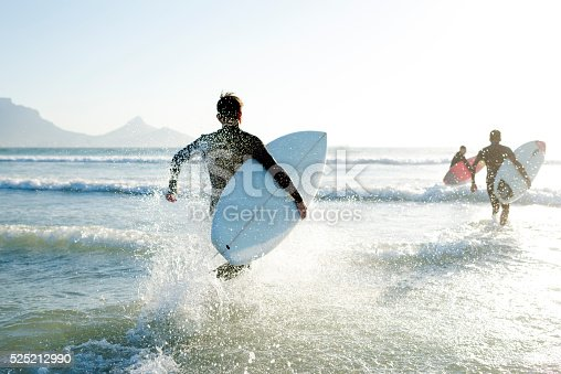 Three teenage boys wearing their wetsuits carrying their surfboards run into the sea on a sunny Summers day.