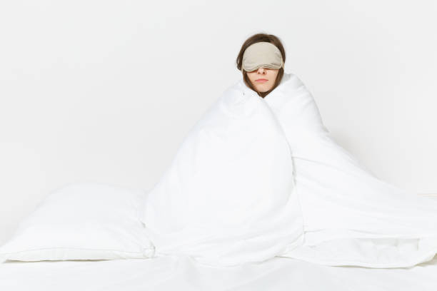Fun tired young woman sitting in bed with sleep mask, sheet, pillow, wrapping in blanket isolated on white background. Beauty female spending time in room. Rest, relax, good mood concept. Copy space. stock photo