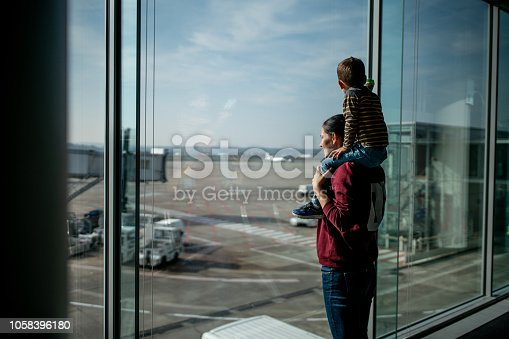Mother and son waiting for the flight at the airport gate and looking at the planes on the runway