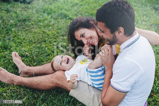 Young parents with their cute baby boy on the grass