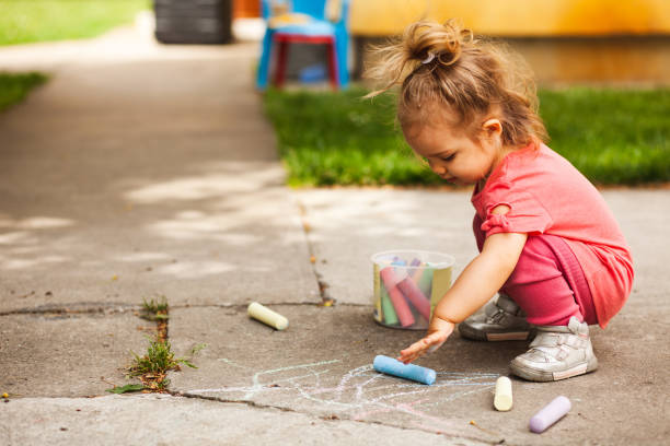 Fun with chalks for a girl in her back yard stock photo