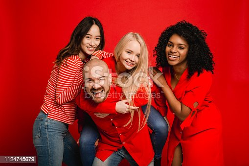 Small group of mixed aged friends having fun together. They're standing infront of a red studio background.