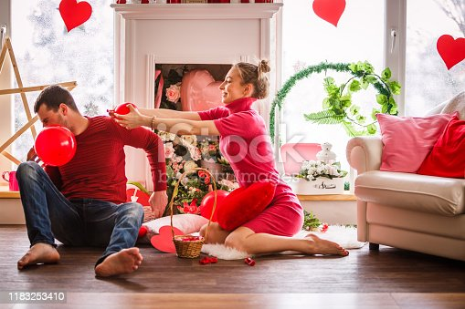 Full length shot of happy young couple sitting on the floor in the living room and having fun while blowing up balloons to set them as Valentine's day decoration.
