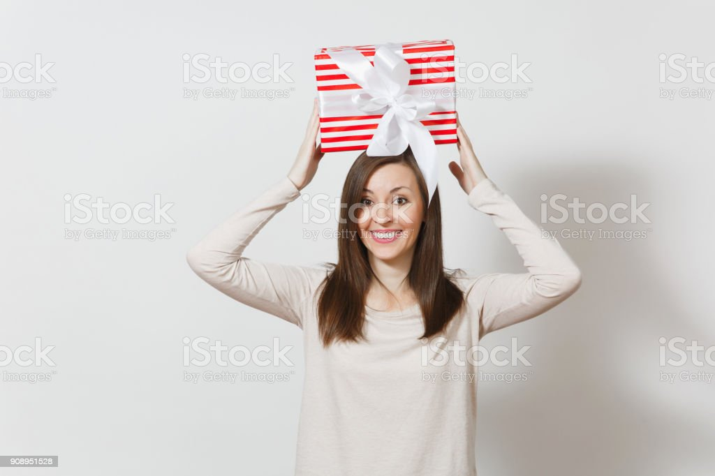 Fun woman holding above her head red striped present box with ribbon isolated on white background. For advertisement. St. Valentines Day, International Women's Day, Christmas birthday, holiday concept stock photo