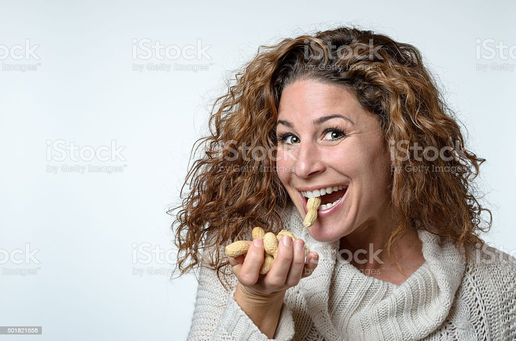 Fun young woman with a peanut in her mouth stock photo