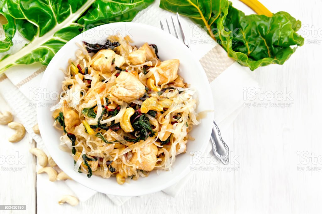 Funchoza with chard and cashew in bowl on board top stock photo
