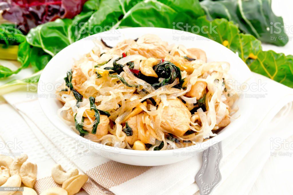 Funchoza with chard and cashew in bowl on light board stock photo