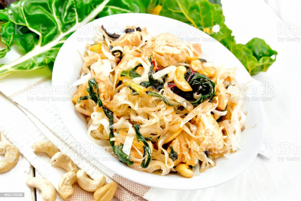 Funchoza with chard and meat in bowl on board stock photo