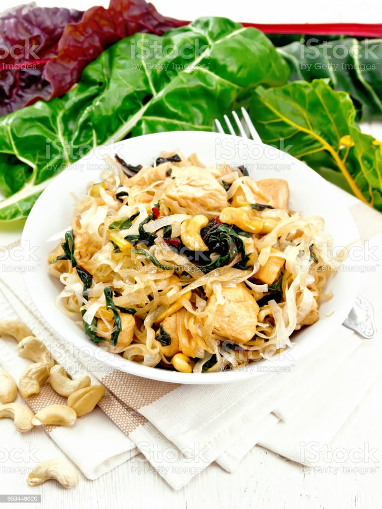 Funchoza with chard and meat in bowl on light board stock photo