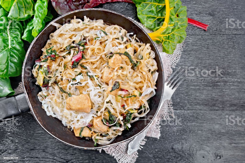 Funchoza with chard and meat in pan on board top stock photo