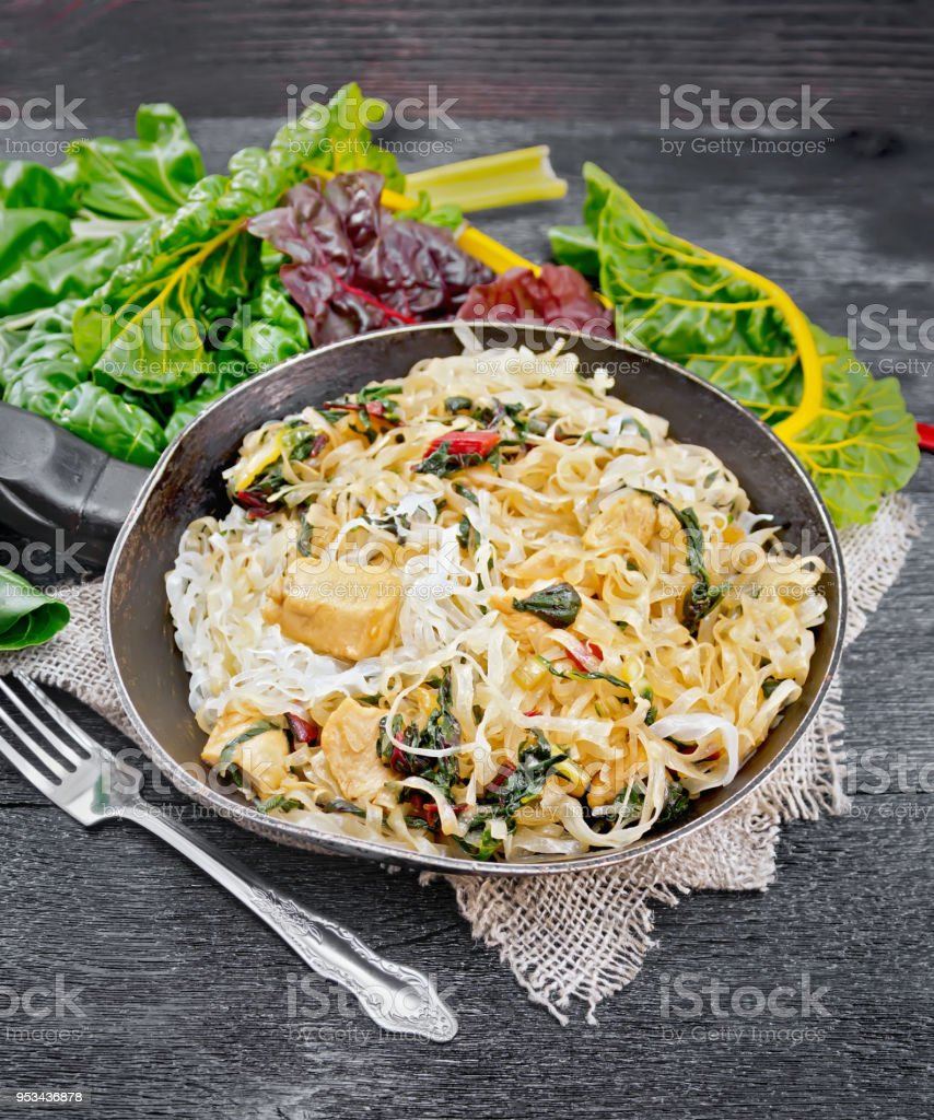 Funchoza with chard and meat in pan on wooden board stock photo