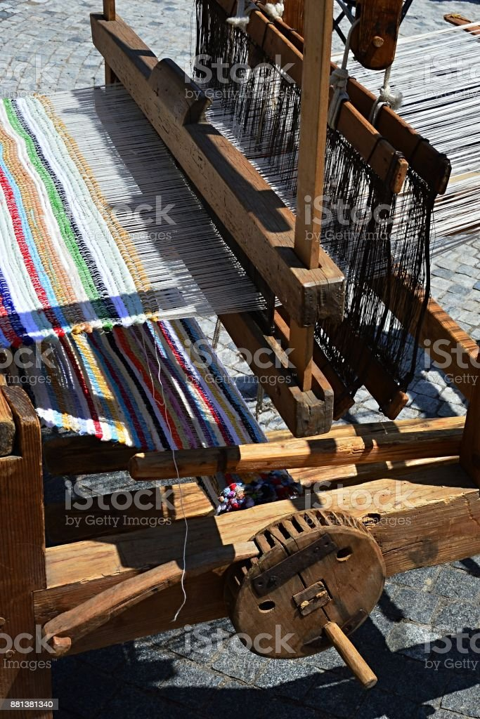 Functional historical wooden hand-loom weaving colorful mat with vertical lines displayed on festival of medieval and traditional crafts stock photo