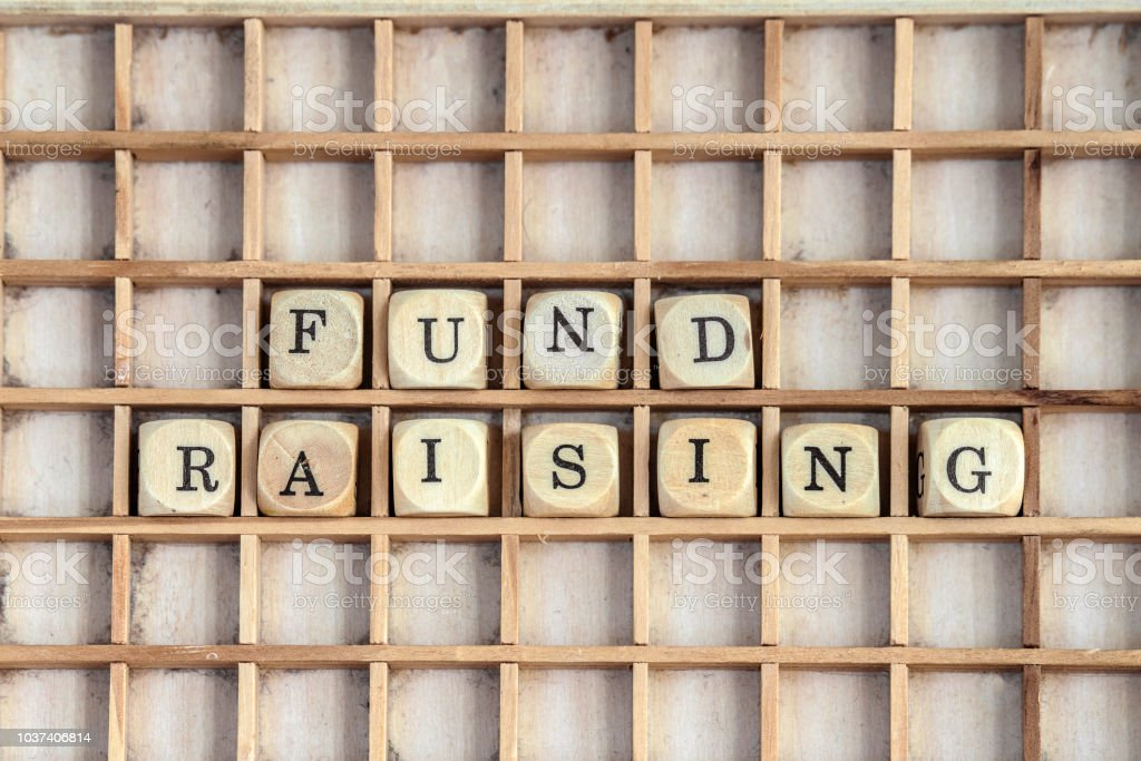 Fund raising sign made of dices on a dirty shelf stock photo